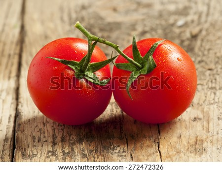 fresh red tomatoes with drops of water on wooden table, selective focus - stock photo