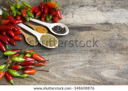 fresh red, yellow and green chilli on old wood background. selective focus image, space for advertising text - stock photo