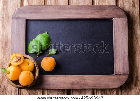 Fresh ripe apricots in wood bowl on vintage slate chalk board background. Selective focus. Background with place for some text. Top view - stock photo