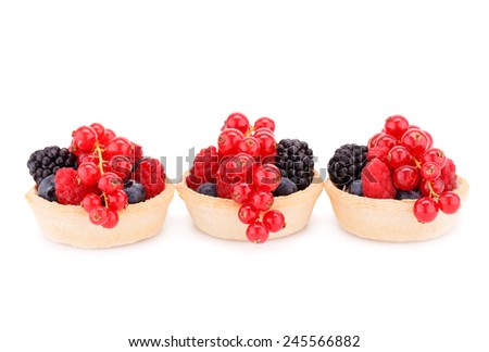 Fresh ripe berries in tartlets isolated on white background. - stock photo