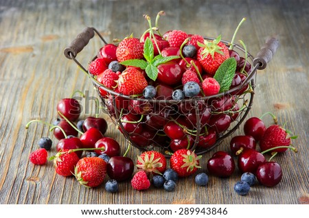 Fresh ripe berries mix, cherries, raspberries, blueberries in vintage basket, summer harvest concept, vitamins, healthy food, vegan ingredients - stock photo