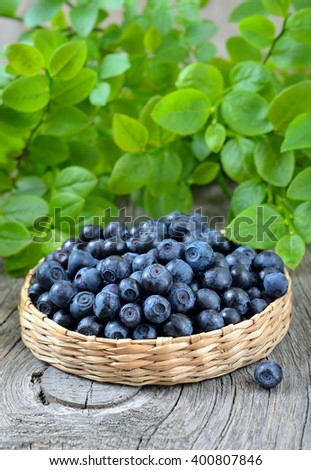 Fresh ripe blueberries in basket on wooden table