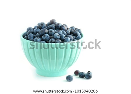 Fresh ripe blueberries in pretty gren bowl on white background with room for text