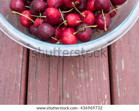 Fresh ripe cherries in glass bowl on red wood background, top view, with copy space - stock photo