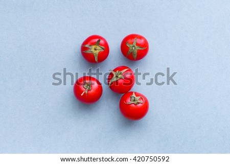 Fresh ripe cherry tomatoes on blue background, top view - stock photo