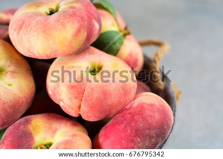 Fresh ripe chinese flat saturn organic peaches with leaves