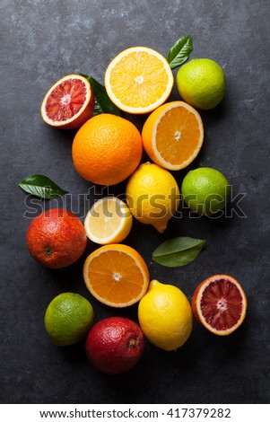 Fresh ripe citruses. Lemons, limes and oranges on dark stone background. Top view - stock photo