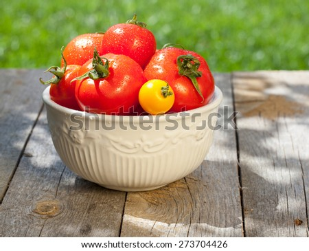 Fresh ripe colorful tomatoes in bowl on wooden table - stock photo