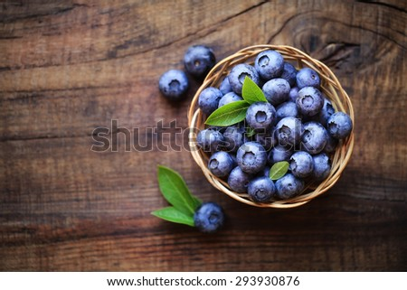 Fresh ripe garden blueberries in a wicker bowl on dark rustic wooden table. with copy space for your text - stock photo