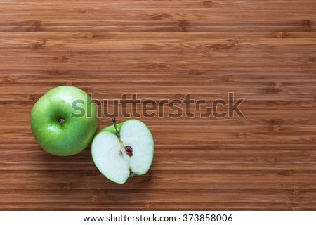 Fresh ripe green apple Granny Smith: whole and sliced in half on a wooden cutting board. Nature fruit concept. Background for healthy diet themes. - stock photo