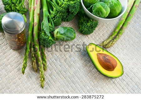 Fresh ripe juicy and delicious vegetables brocolli, brussels sprouts, bunch of asparagus, avocado cut in halves, herbs and spices on a wickered mat on a table ready to be cooked - stock photo