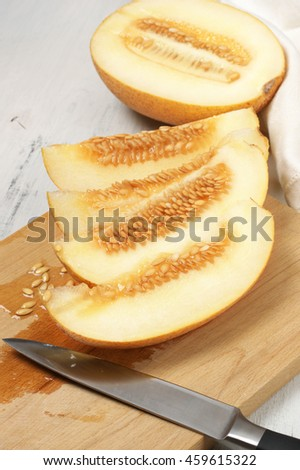 Fresh ripe juicy sliced melon with knife on wooden cutting board.  - stock photo