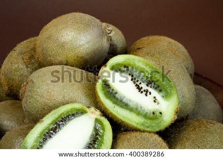 Fresh ripe kiwi in old ceramic plate - stock photo