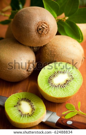 Fresh ripe kiwi with leaves on the wooden table