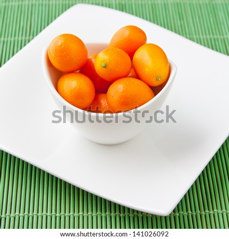 Fresh ripe Kumquats in a bowl. selective focus, shallow dof - stock photo