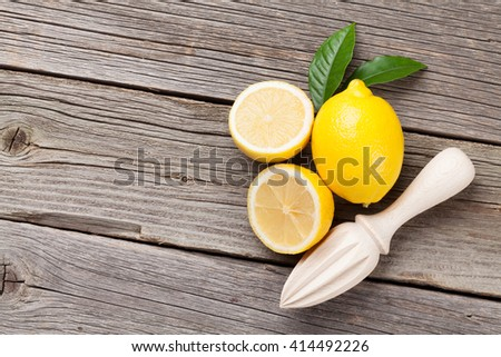 Fresh ripe lemons and juicer on wooden table. Top view with copy space - stock photo