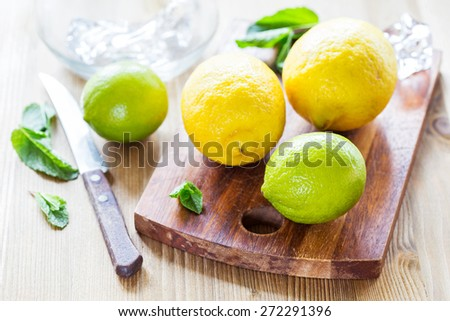Fresh ripe Lemons and Limes with mint on wooden table. - stock photo