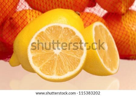 Fresh ripe lemons with half and net bag with lemons - stock photo