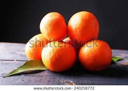 Fresh ripe mandarins on wooden table, on dark  background - stock photo