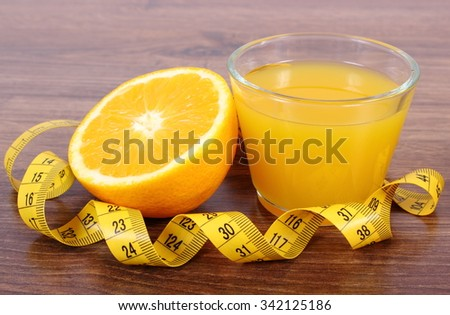 Fresh ripe orange, glass of juice and tape measure on wooden surface plank, healthy lifestyles nutrition and strengthening immunity - stock photo