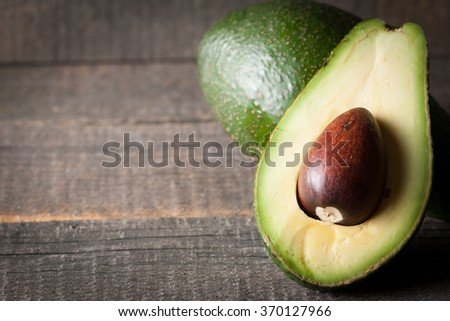 Fresh, ripe, organic avocado on wooden rustic background. Healthy food concept. - stock photo
