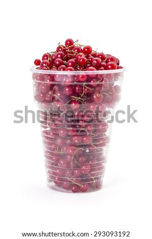 Fresh ripe organic red currants in a plastic glass on a white background