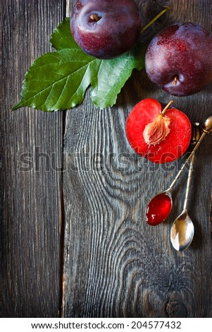 Fresh ripe plums and delicious homemade jam on an old wooden board with place for recipe text. - stock photo