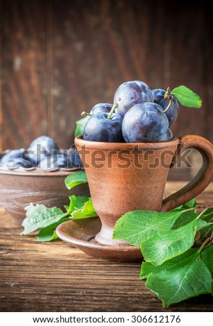 Fresh ripe plums in pottery handmade on a dark wooden background. selective Focus - stock photo