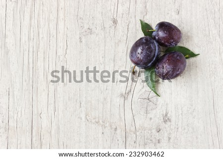 fresh ripe plums on a white textured wooden background.copy space for you text. health and diet food - stock photo