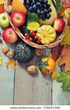 Fresh ripe pumpkins, apples, grape and nuts in wicker basket over wooden background