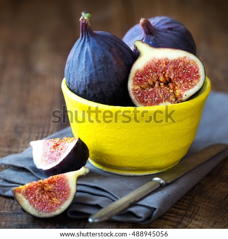 Fresh ripe purple figs in a yellow bowl against dark rustic wooden background
