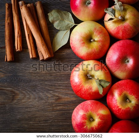 Fresh ripe red apples and cinnamon sticks on wooden background. - stock photo