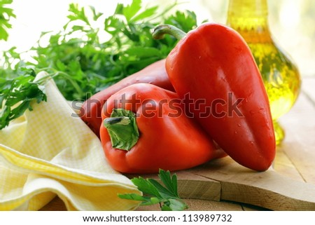 Fresh ripe red bell paprika peppers on a wooden table - stock photo