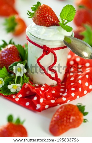 Fresh ripe red farm strawberries with a glass jar of healthy yogurt served on a colorful red country polka dot napkin for a delicious breakfast or appetizer