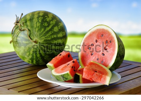 Fresh ripe red juicy watermelons and slices on a wooden table. A green field and a blue sky in background. Healthy eco sweet food rich in vitamins. Popular product of organic farming. - stock photo