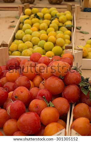 Fresh ripe red plums in a market. - stock photo