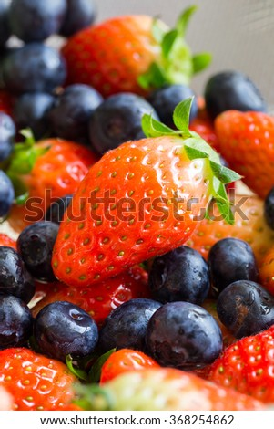 Fresh ripe red strawberries and blueberries in sieve - stock photo