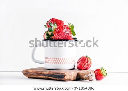 Fresh ripe red strawberries in country style enamel mug on rustic wooden board over white background, selective focus - stock photo