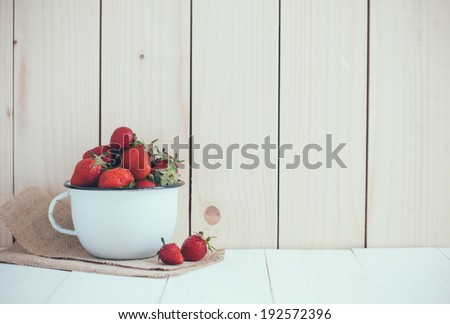 Fresh ripe red strawberries in white enamel mug and rough cloth on wooden background, natural rustic food - stock photo