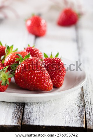 Fresh ripe red strawberries in white plate on white wooden rusti - stock photo
