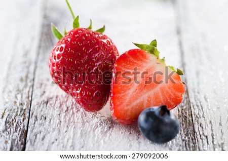Fresh ripe strawberries and blueberries on white wooden background - stock photo