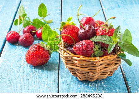 Fresh ripe strawberries and cherries in a wicker basket with mint on a blue painted wooden table. Selective focus - stock photo