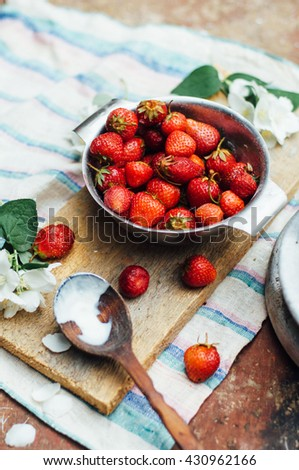 Fresh  ripe strawberries and yellow cherries laid out on the dishes. Fresh strawberries on the rustic table. Preparing jam of berries on wooden background. Top view. Strawberries jam. Rustic styling. - stock photo