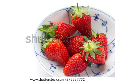Fresh ripe strawberries, source of antioxidants and vitamin C, in a white bowl with blue decorative pattern, to be served as a healthy snack or dessert, high-angle close-up with copy space on white - stock photo