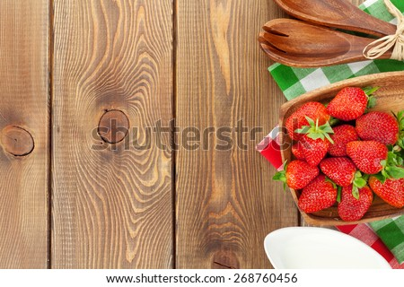 Fresh ripe strawberry in bowl and milk over wooden table background. Top view with copy space - stock photo