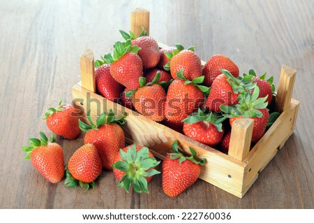 fresh ripe strawberry with crate on rustic table  - stock photo