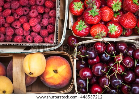 Fresh ripe summer berries and fruits (peaches, apricots, cherry, strawberry) in baskets, top view