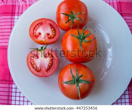 Fresh ripe tomatoes on white dish - top view - stock photo