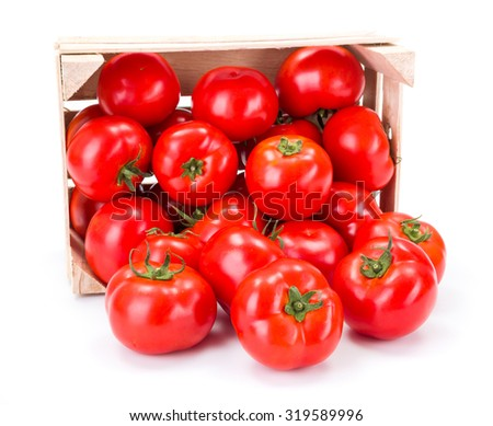 Fresh ripe tomatoes (Solanum lycopersicum) spilled out from wooden crate - stock photo