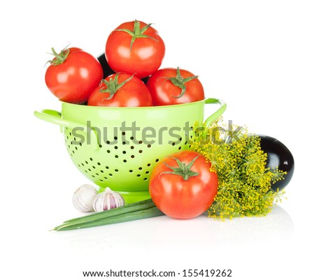 Fresh ripe vegetables in colander. Isolated on white background